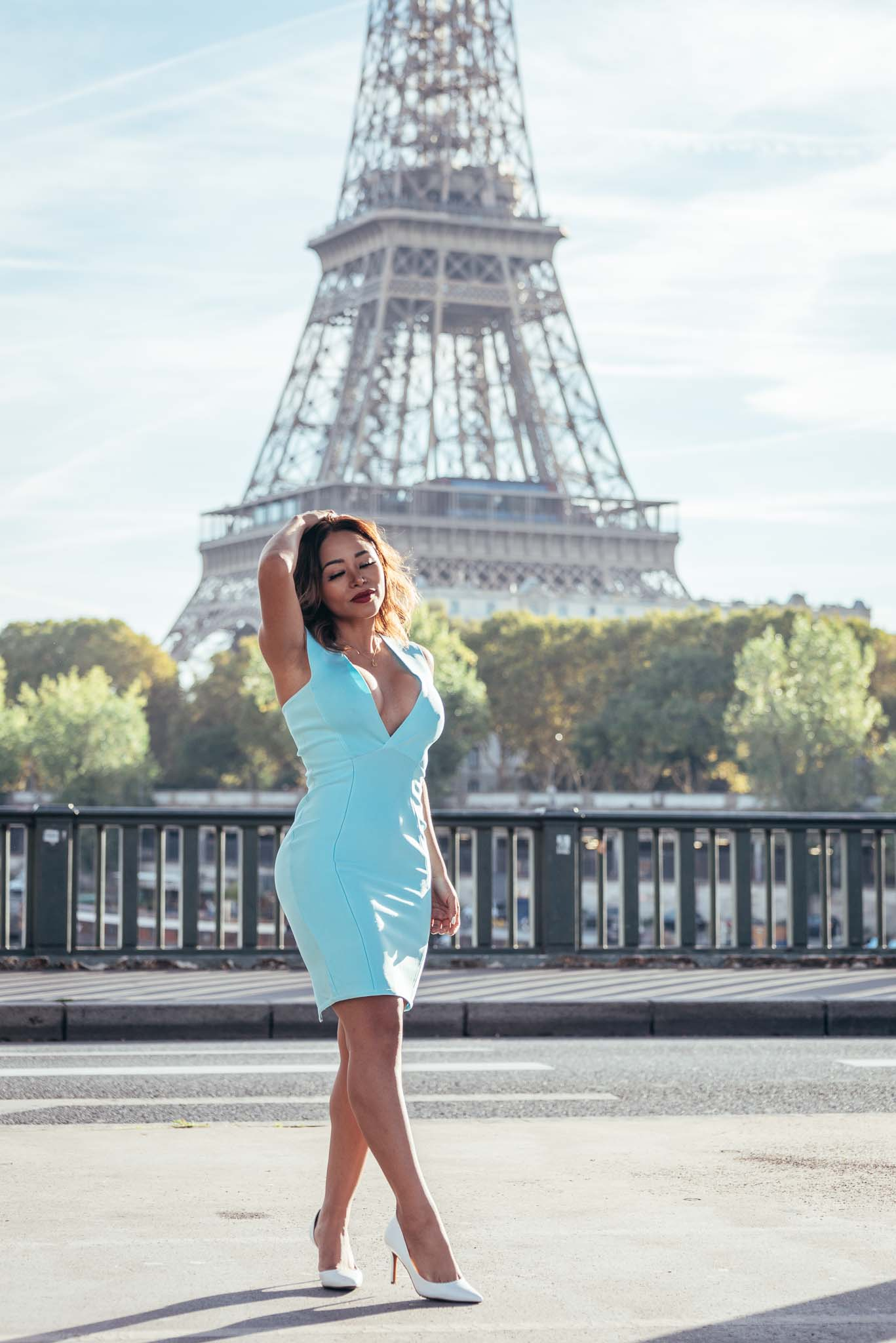 Portrait of instagram influencer in a blue dress in front of the Eiffel Tower in Paris