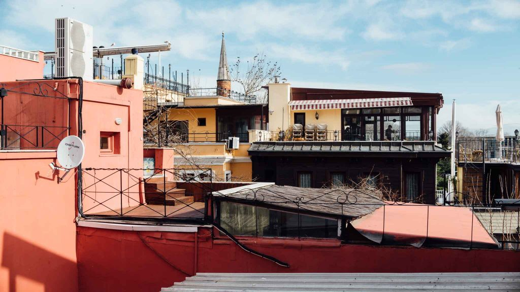 A salmon pink building and other rooftops in Istanbul, Turkey. Travel photography by Paige Gribb
