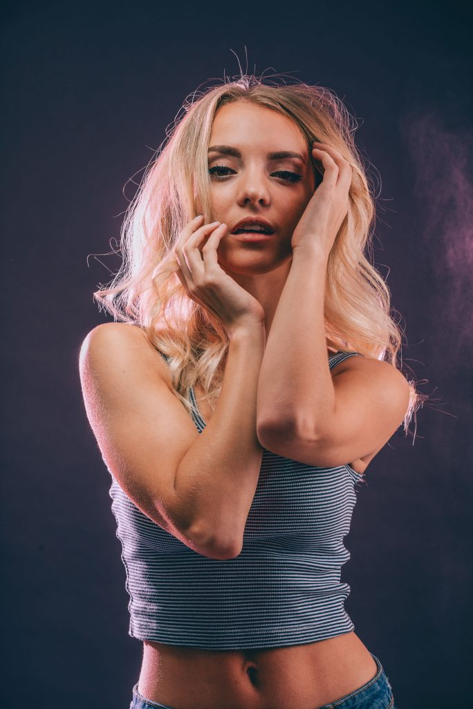 Studio portrait photography of model Anna Hrehlevych in a striped crop top against a navy and pink background with her hands by her face