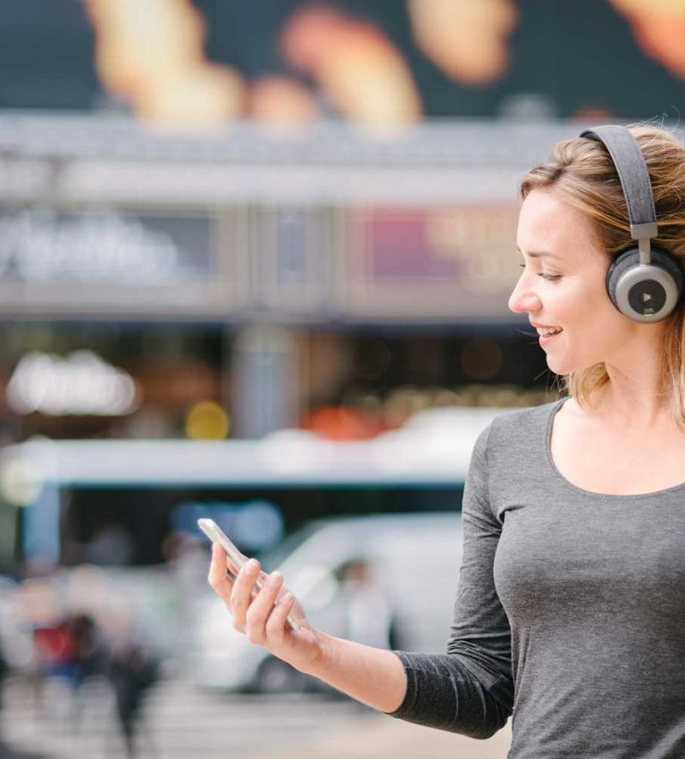 lifestyle product photo of a model wearing Orosound headphones in Paris with a busy Parisian street behind her