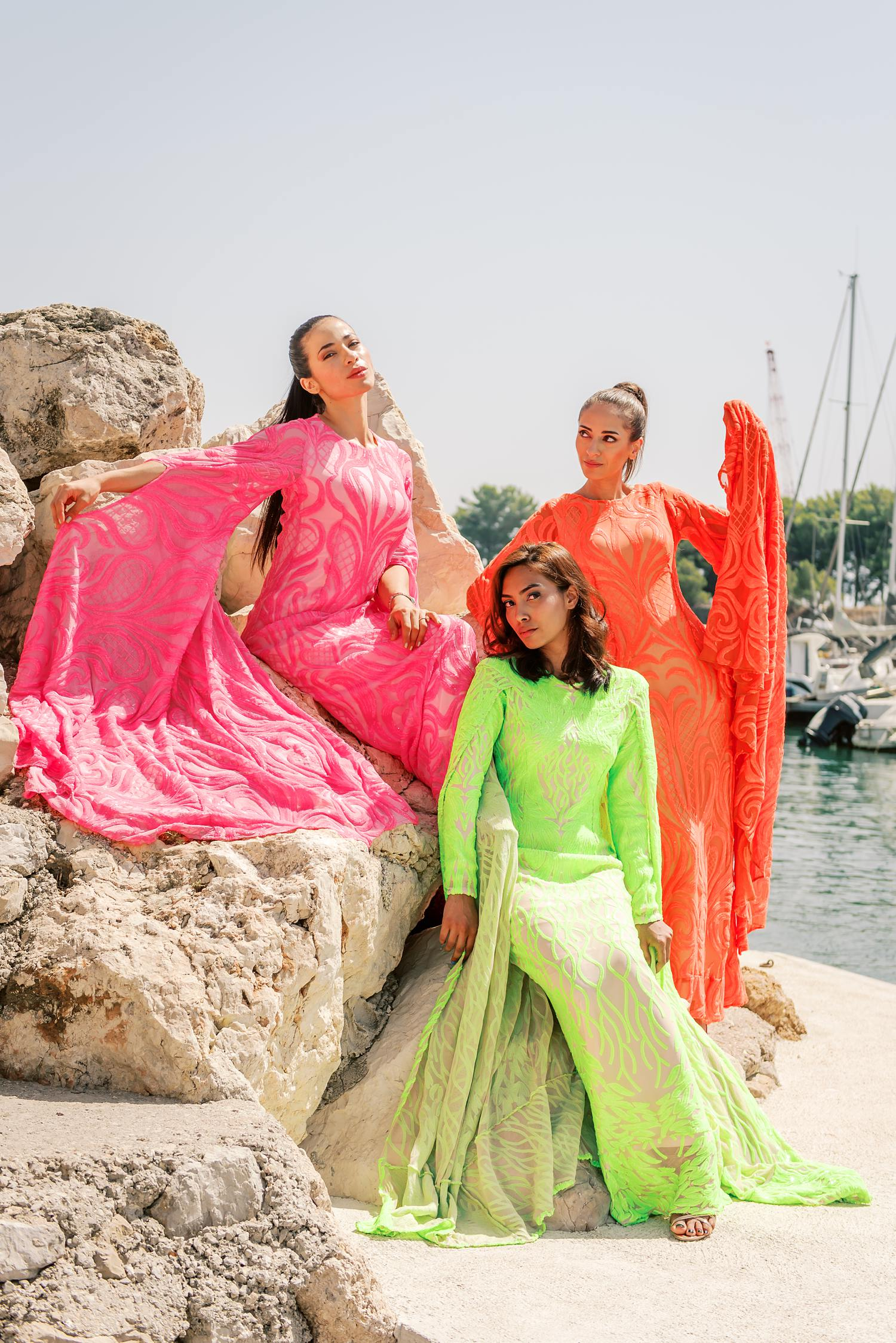 fashion advertorial shot of three models in haute couture custom beaded gowns sitting on the rocks at a harbor in Marseille, France