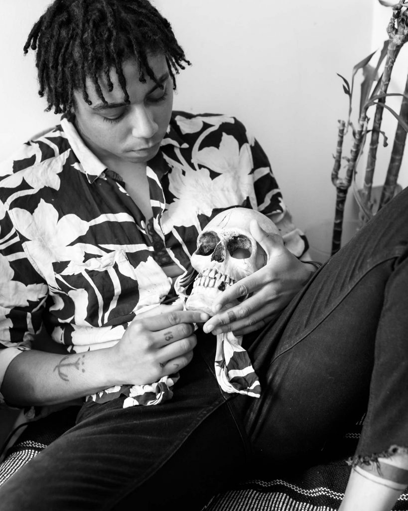 black and white photo of androgynous model in a bold printed shirt and holding a skull