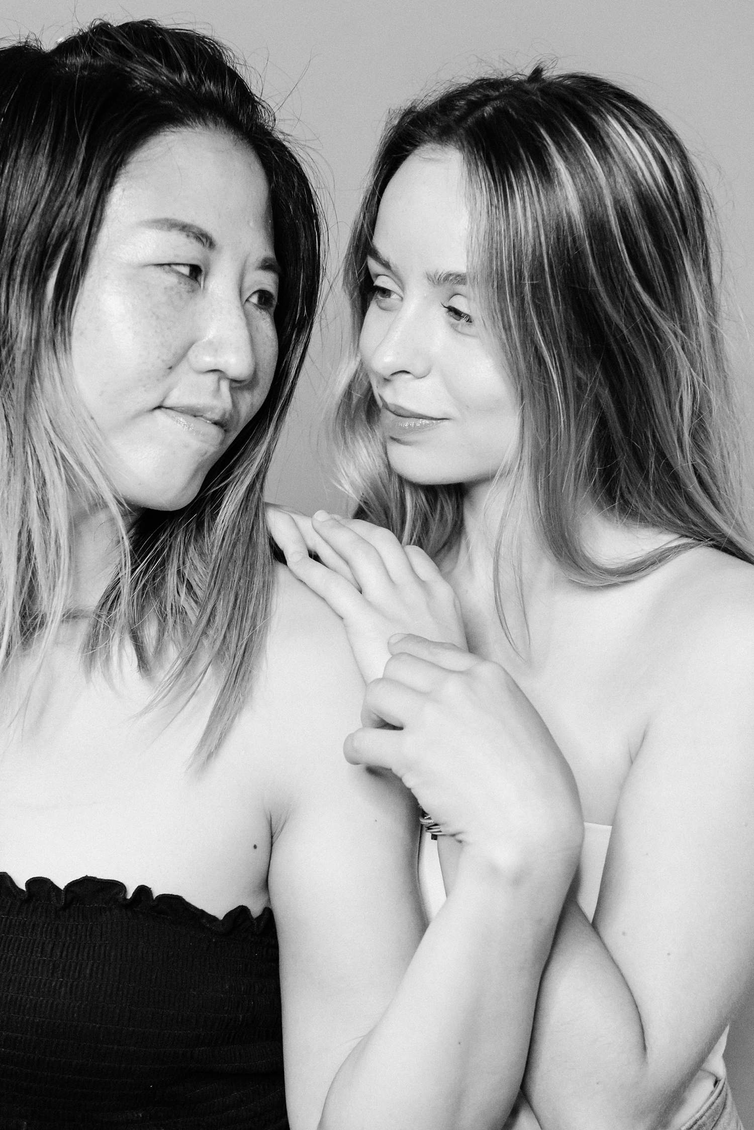 black and white studio portrait of two women sharing a gaze