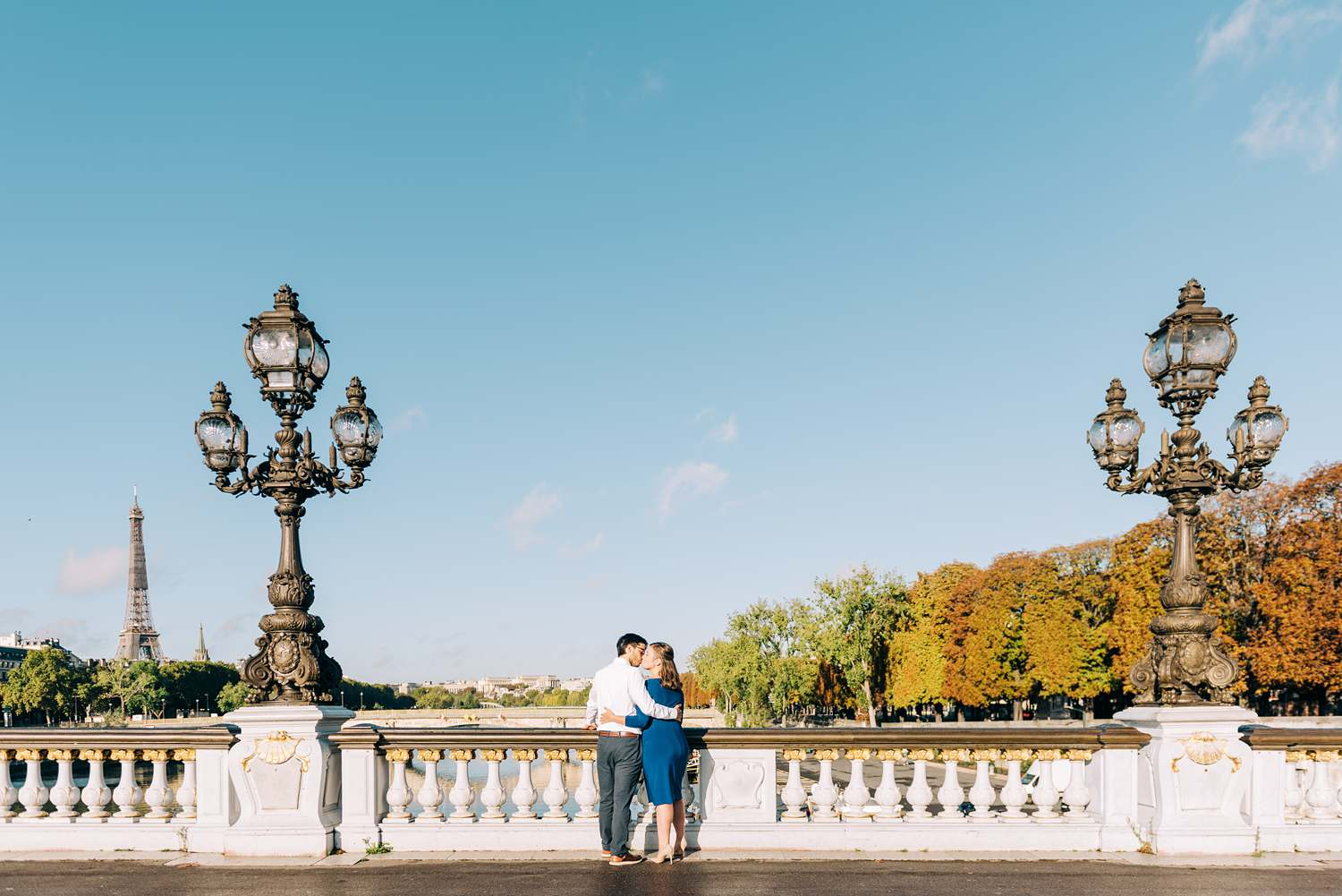 engagement photography session in paris on the pont alexandre iii bridge, wide shot with the couple kissing in the center and the eiffel tower in the distance on a sunny day