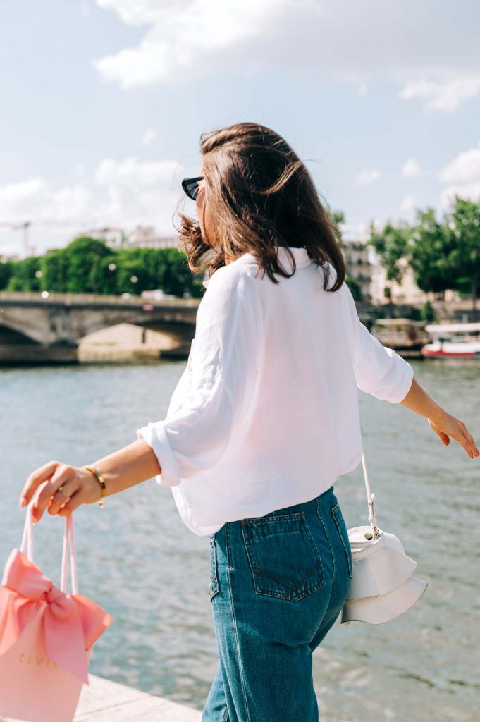 windswept lifestyle image of model on the banks of the seine wearing elvie jewelry and carrying the brand's small shopping bag as she walks