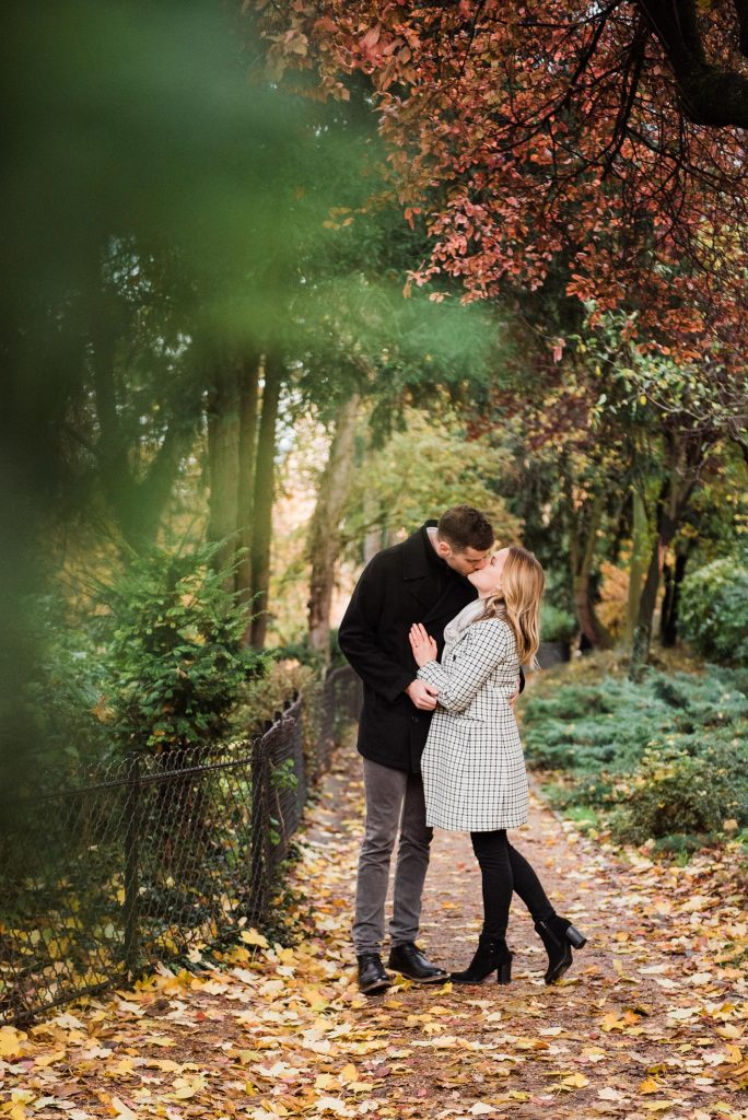 photo of couple kissing on a garden pathway at the beginning of fall with trees just starting to turn: part of an engagement photography session in Paris