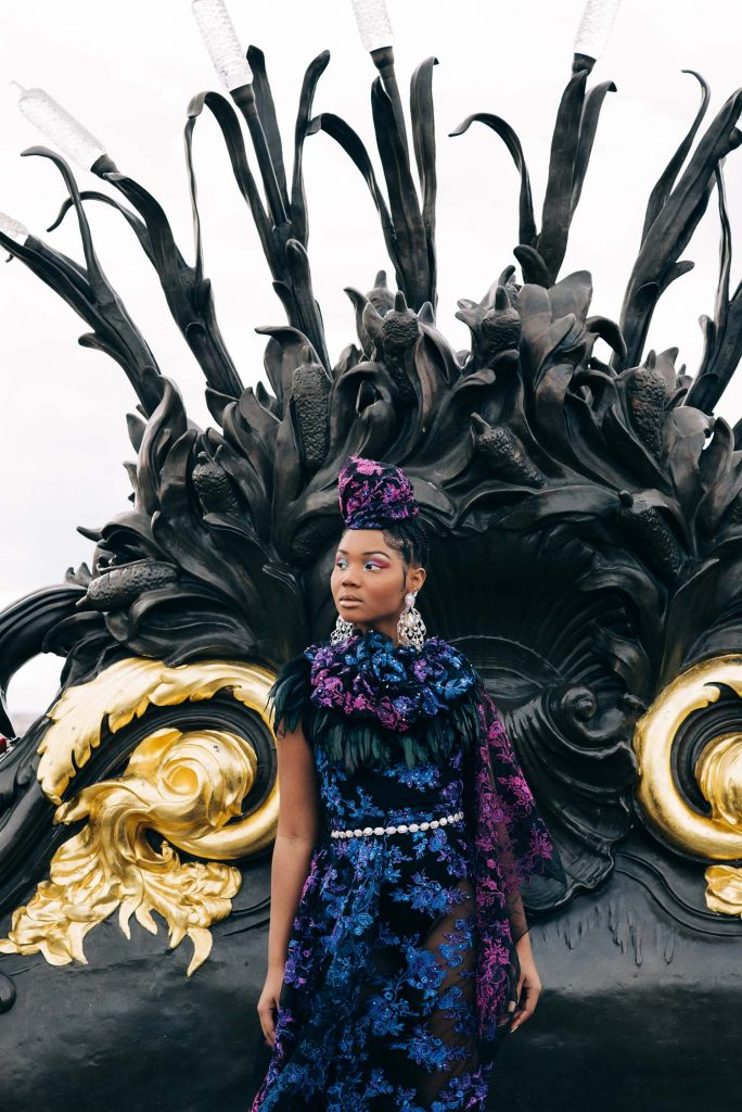fashion photography image of a model in a black, blue, and purple embroidered gown with feathers, standing in front of an ornate wrought iron and gold fixture in Paris, France