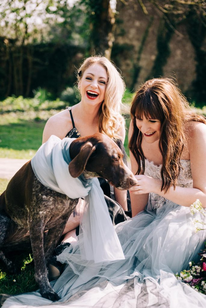lifestyle photo of two women in ornate gowns sitting in the grass and laughing as they play with a dog
