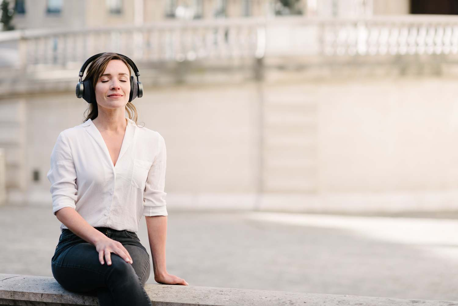 brand photography for french headphone startup Orosound. Model with eyes closed wearing headphones in a peaceful area in Paris, France
